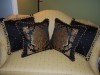 Beautiful black pillows with trim and a mitered frame surrounding the  floral inset.