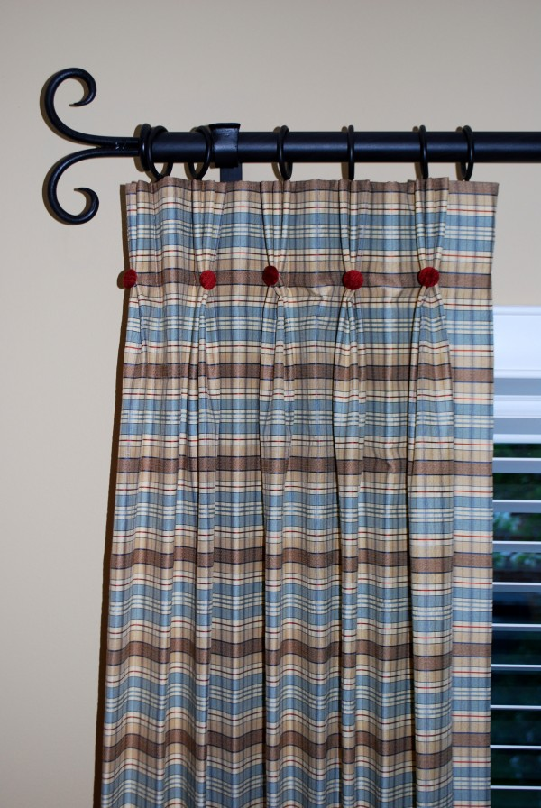 Close up of pinch pleat drapes with contrast covered buttons.